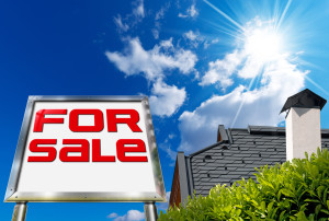 "Large chrome billboard with written ""for sale"" on blue sky with roof, clouds and sun rays"